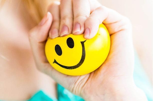 Woman-holding-smiley-face-stress-ball